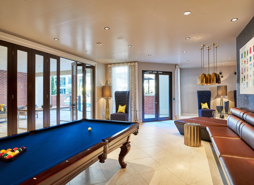 View of Resident Lounge, Showing Pool Table, Seating Areas, and Window Views at 3800 Main Apartments